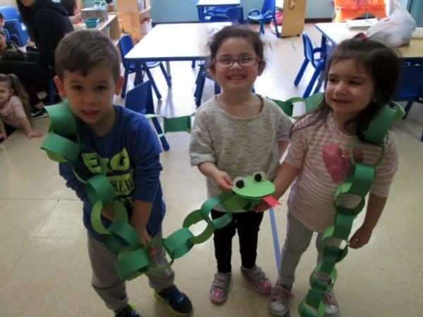 Three Year Olds with a long green paper ring snake