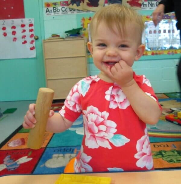 Tiny tot enjoying simple wooden toy